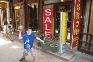 Eitan playing catch with a coconut while the girls shop - Hauz Khaz village, Delhi.